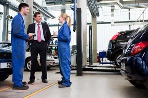 Businessman with two car mechanics in repair garageの写真素材 [FYI03479222]