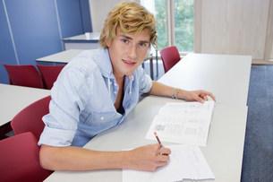 University student writing on exam paper in classの写真素材 [FYI03479257]