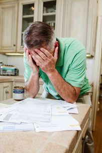 Mature man with head in hands over table of household billsの写真素材 [FYI03479276]