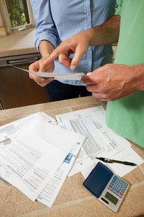 Mature couple looking at household bills, close upの写真素材 [FYI03479278]