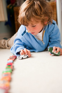 Young boy lining up toy cars in his bedroomの写真素材 [FYI03479319]