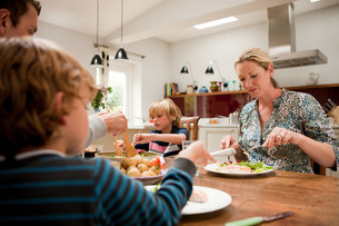 Family sitting down and eating a healthy meal togetherの写真素材 [FYI03479340]