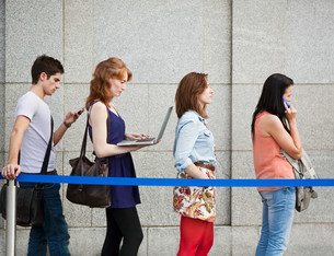 Four people in a queue, one using a laptopの写真素材 [FYI03479368]
