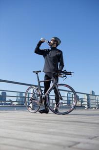Man quenching thirst behind his racing bikeの写真素材 [FYI03479489]