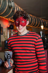 Young man in costume and mask in bar, portraitの写真素材 [FYI03479599]