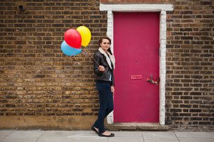 Young woman holding colourful balloons against brick wallの写真素材 [FYI03479607]