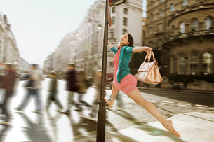 Mid adult woman in pink dress leaping through city streetsの写真素材 [FYI03479670]