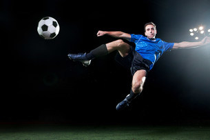 Young soccer player leaping into air to kick ballの写真素材 [FYI03479755]