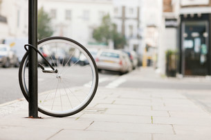 Single bicycle wheel secured to lamp postの写真素材 [FYI03479776]