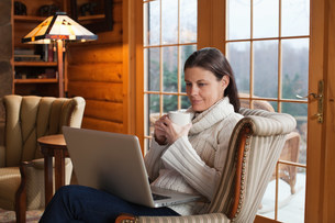 Mature woman relaxing in armchair with laptopの写真素材 [FYI03479792]