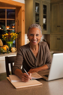 Mature woman using laptop and wearing ear phones, portraitの写真素材 [FYI03479810]