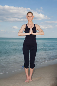Mid adult woman in yoga pose on beachの写真素材 [FYI03479824]