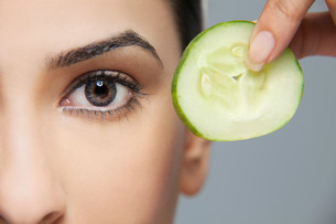 Woman with a cucumber next to her eyeの写真素材 [FYI03479871]