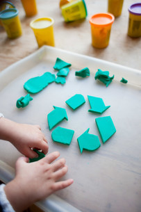 Child making recycling symbol from play clayの写真素材 [FYI03479926]