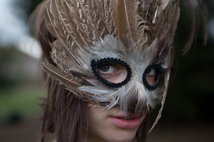 Young woman wearing a mask of feathersの写真素材 [FYI03479937]