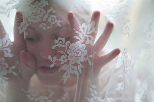 Young woman behind lace curtainの写真素材 [FYI03479949]