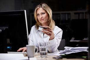 Businesswoman in dark office, using credit card onlineの写真素材 [FYI03480053]
