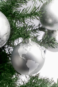 Silver globe bauble on christmas treeの写真素材 [FYI03480073]