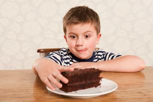 Boy reaching for chocolate cakeの写真素材 [FYI03480216]