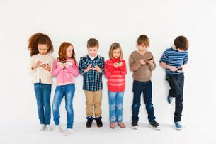 Children using smartphones, standing in a rowの写真素材 [FYI03480241]