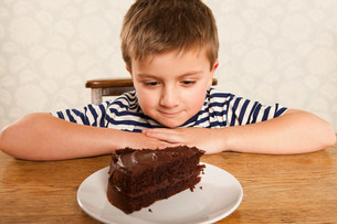 Boy looking at slice of chocolate cakeの写真素材 [FYI03480253]