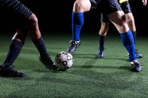 Soccer players tackling on pitch, low sectionの写真素材 [FYI03480415]