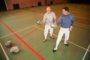 Senior and mature men fencing togetherの写真素材 [FYI03480517]