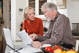 Senior couple looking concerned with bills and laptopの写真素材 [FYI03480636]