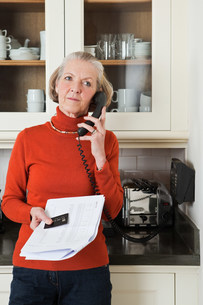 Senior woman on telephone with statement and credit cardの写真素材 [FYI03480637]