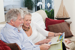 Senior couple looking at travel brochureの写真素材 [FYI03480649]