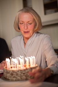Senior woman blowing out candles on birthday cakeの写真素材 [FYI03480667]