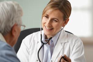 Doctor taking senior mans blood pressure, close upの写真素材 [FYI03481181]