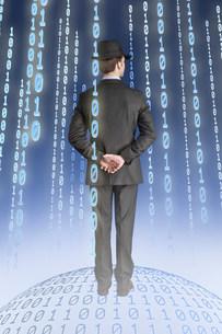 Businessman standing on binary globe with binary stringsの写真素材 [FYI03481230]