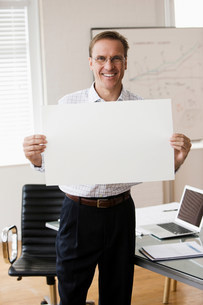 Mature businessman holding blank page in officeの写真素材 [FYI03481460]