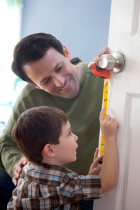 Father and son measuring door at homeの写真素材 [FYI03481462]