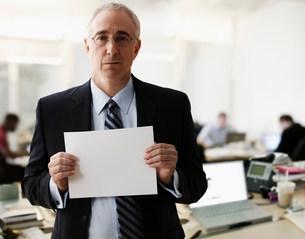 Portrait of senior man holding blank sheet of paperの写真素材 [FYI03481501]
