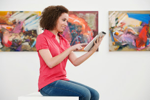 Young woman using digital tablet in art galleryの写真素材 [FYI03481528]