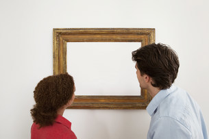 Young couple looking at blank image in picture frameの写真素材 [FYI03481552]