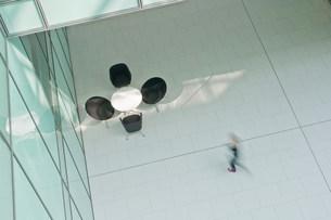 Woman walking across floor in office blockの写真素材 [FYI03481686]