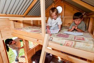 Mother looking in on children in playhouseの写真素材 [FYI03481768]
