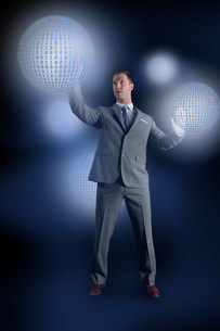 Businessman interacting with holographic binary globesの写真素材 [FYI03481779]