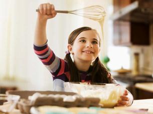 Girl mixing cake batter in bowlの写真素材 [FYI03481820]