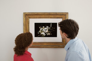 Young couple looking at print in picture frameの写真素材 [FYI03481827]