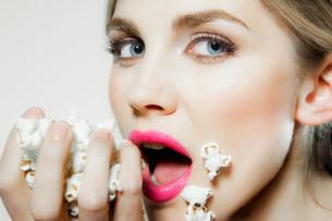 Young woman eating popcornの写真素材 [FYI03481999]