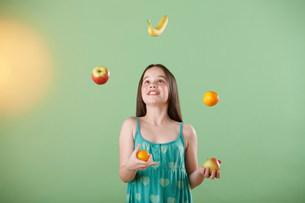 Girl juggling fruitの写真素材 [FYI03482258]