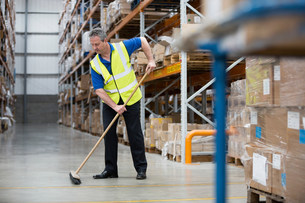 Man sweeping warehouse floor with broomの写真素材 [FYI03482294]