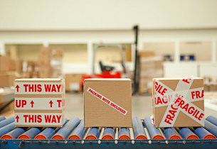 Three cardboard boxes with parcel tape on conveyor beltの写真素材 [FYI03482412]