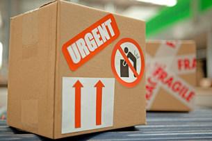 Cardboard box with warning stickers on conveyor beltの写真素材 [FYI03482413]