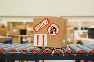 Cardboard box with warning stickers on conveyor beltの写真素材 [FYI03482418]