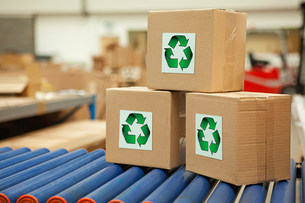 Cardboard boxes with recycling symbols on conveyor beltの写真素材 [FYI03482419]